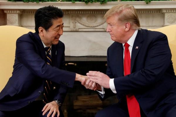 Perdana Menteri Jepang Shinzo Abe (kiri) berjabat tangan dengan Presiden AS Donald Trump di Gedung Putih, Washington, AS, Jumat (26/4/2019). - Reuters/Kevin Lamarque