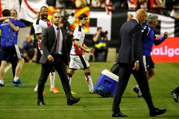 Pelatih Rayo Vallecano Paco Jemez (kiri) berjalan ke arah pelatih Real Madrid Zinedine Zidane yang berjalan tertunduk lesu selepas pertandingan yang berakhir dengan kemenangan Rayo 1 - 0. - Reuters/Javier Barbancho