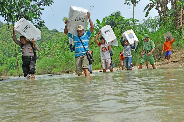 Petugas memanggul kotak suara menuju Tempat Pemungutan Suara (TPS) terpencil di Dusun Nampu, Desa Pojok Klitih, Kecamatan Plandaan, Jombang, Jawa Timur, Selasa (16/4/2019). KPPS harus memutar melewati Kabupaten Nganjuk sepanjang 30 kilometer dan harus menyeberangi sungai untuk sampai di dusun Nampu.ANTARA FOTO - Syaiful Arif