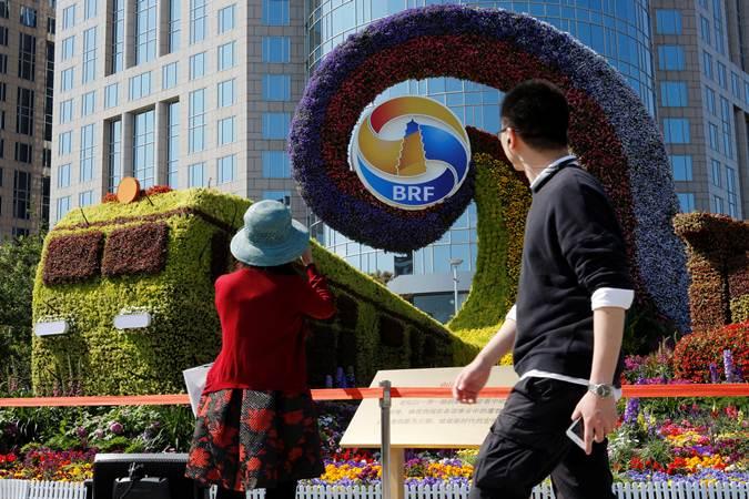 Ilustrasi-Seorang perempuan mengabadikan logo Belt and Road Forum (BRF), di Beijing, China, Kamis (25/4/2019). - Reuters/Florence Lo