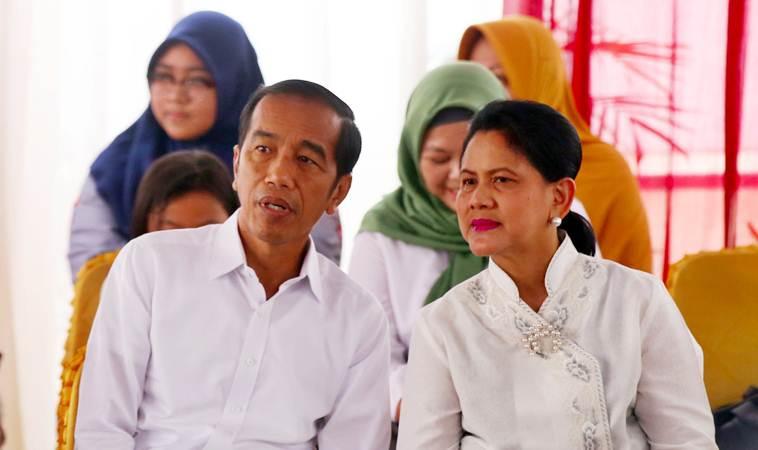 Presiden Joko Widodo (kiri) didampingi Ibu Negara Iriana Joko Widodo menunggu antrean saat menggunakan hak pilihnya di TPS 008, Gambir, Jakarta, Rabu (17/4/2019). - Bisnis/Abdullah Azzam