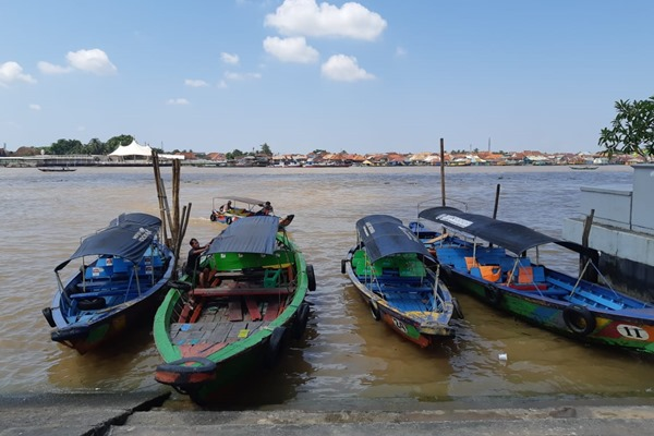 Sejumlah perahu motor kecil berjajar di pinggiran sungai. Perahu yang biasa disebut ketek tersebut siap mengantar wisatawan untuk menyusuri Sungai Musi. - Bisnis/Tim Jelajah Infrastruktur Sumatra 2019