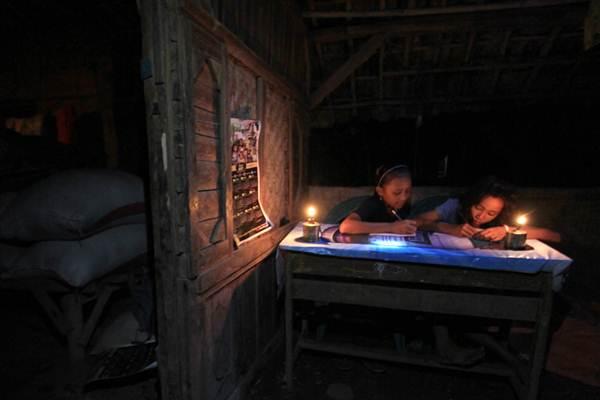Dua anak belajar dengan penerangan lampu minyak di Dusun Cagakroya, Cikamurang, Terisi, Indramayu, Jawa Barat, Rabu (3/5). - Antara/Dedhez Anggara