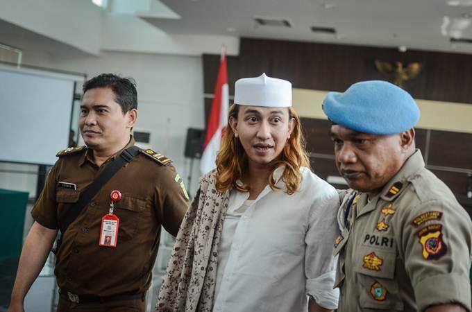 Terdakwa kasus dugaan penganiayaan terhadap remaja Bahar bin Smith (kiri) berjalan keluar ruangan seusai menjalani sidang lanjutan dengan agenda pemeriksaan saksi di Gedung Perpustakaan dan Kearsipan Kota Bandung, Jawa Barat, Kamis (18/4/2019). - ANTARA/Raisan Al Farisi
