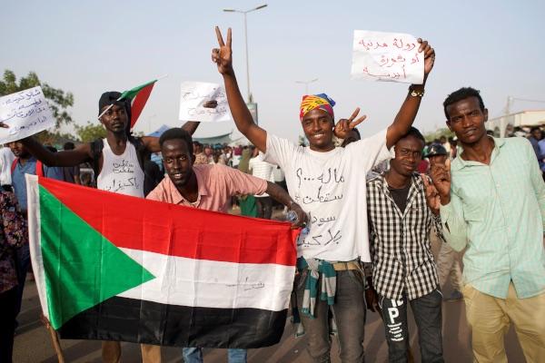 Pengunjuk rasa memegang bendera Sudan dan melantunkan slogan-slogan dalam protes terhadap pengumuman militer yang menyatakan bahwa Presiden Omar Al Bashir bakal digantikan oleh pejabat militer, di luar Kementerian Pertahanan di Khartoum, Sudan, Kamis (11/4/2019). - Reuters/Stringer