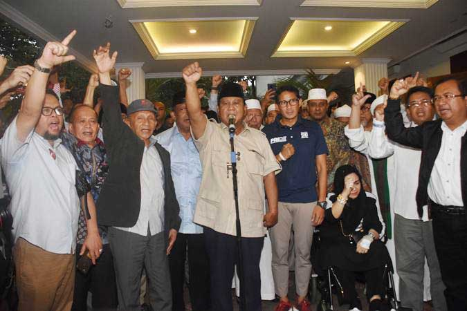 Capres nomor urut 02 Prabowo Subianto (tengah) bersama Cawapres Sandiaga Uno dan petinggi partai pendukung mengangkat tangan saat mendeklarasikan kemenangannya pada Pilpres 2019 kepada awak media di kediaman Kertanegara, Jakarta, Kamis (18/4/2019). - ANTARA/Indrianto Eko Suwarso