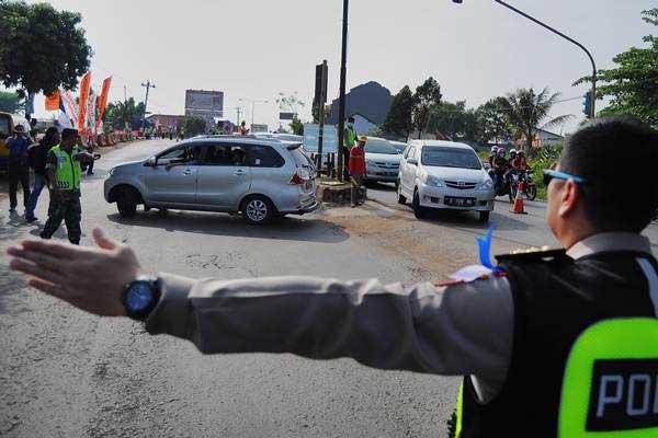 Petugas kepolisian mengatur lalu lintas kendaraan pemudik yang akan memasuki tol di pintu keluar tol Gringsing, Kabupaten Batang, Jawa Tengah, Kamis (29/6/2017). - Antara/Harviyan Perdana Putra