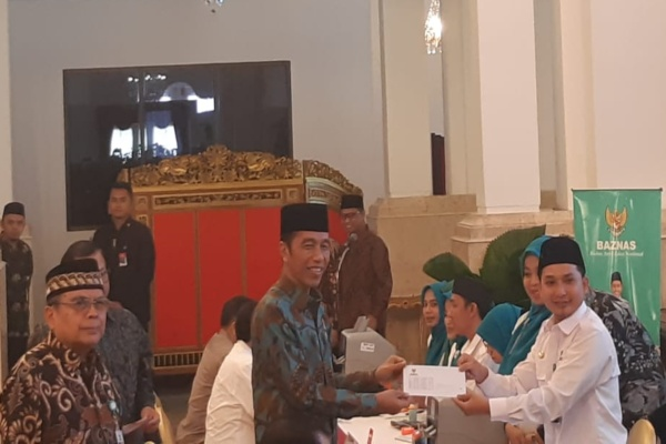 Presiden Joko Widodo menerima bukti peneyerahan zakat dari petugas Baznas. - Bisnis/Yodie Hardiyan