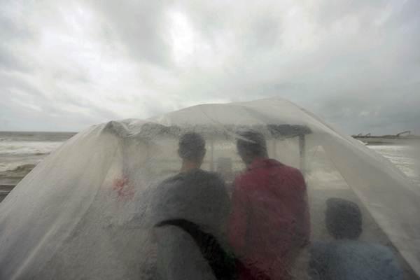Warga berteduh saat hujan - Reuters/Dinuka Liyanawatte
