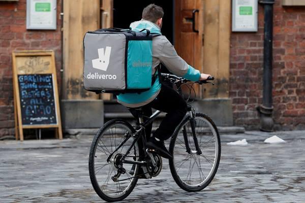 Seorang pekerja Deliveroo mengayuh sepeda melalui sebuah jalan di Liverpool, Inggris pada 18 Oktober 2017. - REUTERS/Phil Noble