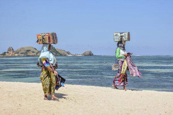 Sejumlah pedagang kain tenun melintas di kawasan wisata Kuta Beach Park The Mandalika di Desa Kuta, Kecamatan Pujut, Praya, Lombok Tengah, NTB, Jumat (17/5/2019). Pemerintah menargetkan kunjungan wisatawan ke NTB pada 2019 sebanyak 4 juta wisatawan yang terdiri dari 2 juta wisatawan mancanegara dan 2 juta wisatawan nusantara. - Antara/Ahmad Subaidi