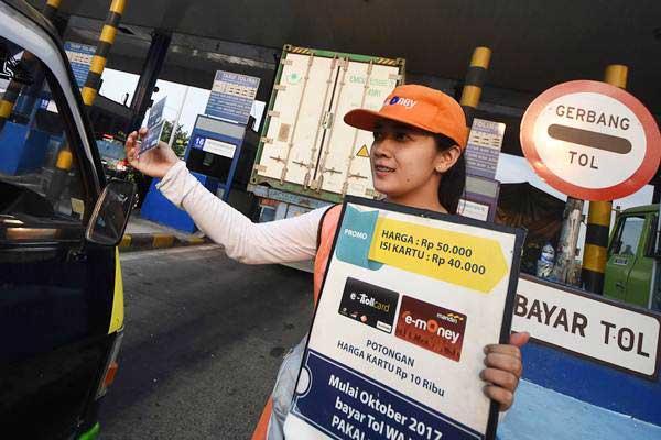 Petugas menawarkan kartu elektronik uang (e-toll) pada pengguna kendaraan roda empat yang melintas di Gerbang Tol Tandes Surabaya, Jawa Timur, Senin (18/9). - ANTARA/M Risyal Hidayat