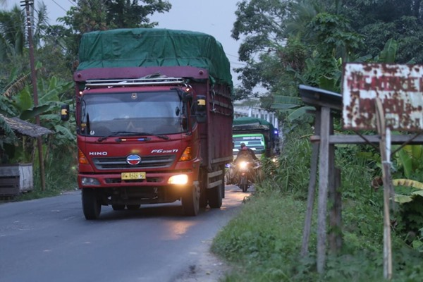 Truk sarat muatan melintasi jalur lintas Sumatra Timur di Kayu Agung, Ogan Komering Ilir, Jumat (3/5/2019). - Bisnis/Tim Jelajah Infrastruktur Sumatra 2019/Abdullah Azzam