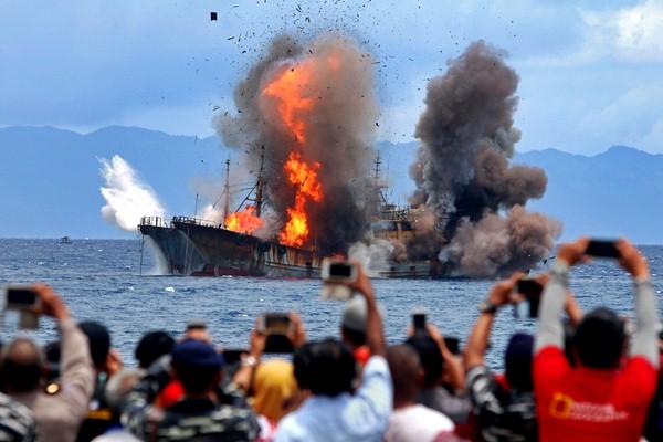 Ilustrasi - Warga menyaksikan proses penenggelaman kapal pelaku pencurian ikan KM SINO 26 dan KM SINO 35 di perairan Desa Morela, Pulau Ambon, Kabupaten Maluku Tengah, Maluku, Sabtu (1/4). - Antara/Izaac Mulyawan