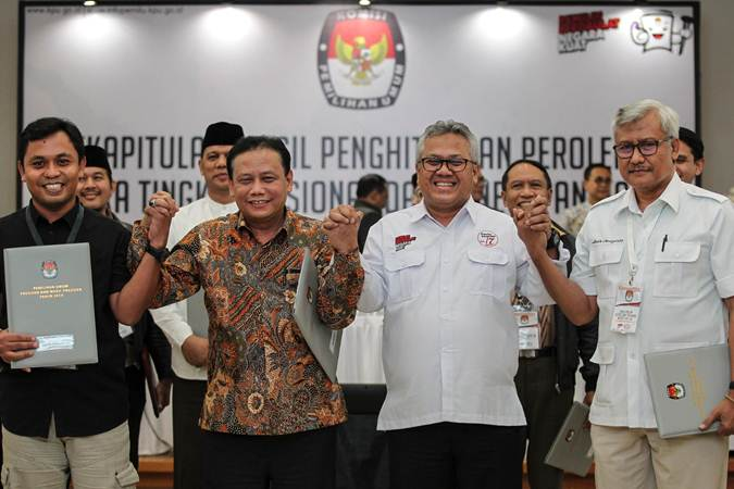 Ketua KPU Arief Budiman (kedua kanan) bersama Ketua Bawaslu Abhan (kedua kiri) bergandengan tangan dengan perwakilan saksi TKN 01 dan BPN 02 usai mengikuti rekapitulasi hasil penghitungan perolehan suara tingkat nasional dan penetapan hasil Pemilu 2019 di gedung KPU, Jakarta, Selasa (21/5/2019) dini hari. - ANTARA/Dhemas Reviyanto