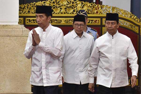 Presiden Joko Widodo (kiri) didampingi Menko Polhukam Wiranto (kanan) dan Menteri Agama Lukman Hakim Saifuddin memberi salam kepada tamu di Istana Negara, Jakarta.  - Antara/Puspa Perwitasari