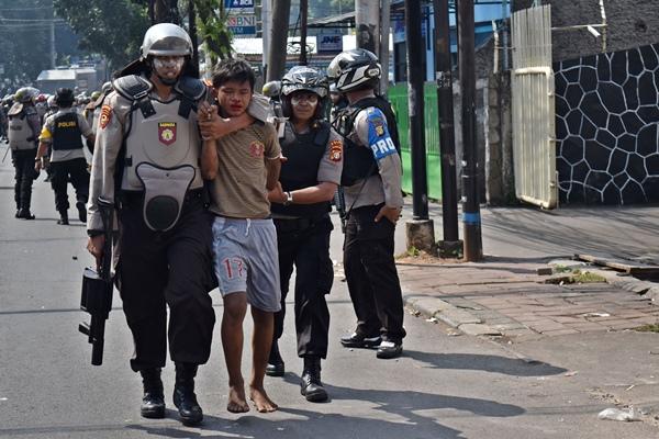 Sejumlah polisi mengamankan salah seorang warga yang diduga ikut aksi kerusuhan di Jalan KS. Tubun, Petamburan, Jakarta Pusat, Rabu (22/5/2019) - ANTARA FOTO/Aditya Pradana Putra