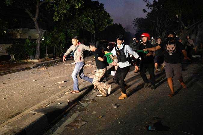 Polisi dan warga menangkap seorang yang diduga menjadi provokator pembakaran mobil di Kompleks Asrama Brimob, Petamburan, Jakarta, Rabu (22/5/2019). - Antara/Sigid Kurniawan