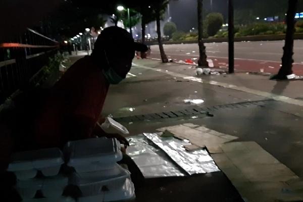 Suwandi masih menjual nasi box-nya sembari melihat keadaan ketika aparat kepolisian mensterilkan sepanjang jalan Thamrin dari massa Aksi Demo 22 Mei - Bisnis/Aziz Rahardyan