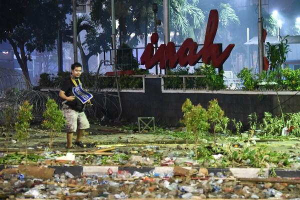 Seorang pria melintas di depan gedung Sarinah, Jakarta, pascarusuh polisi dan massa, Kamis (23/5/2019) dini hari. - ANTARA FOTO / Prasetyo Utomo