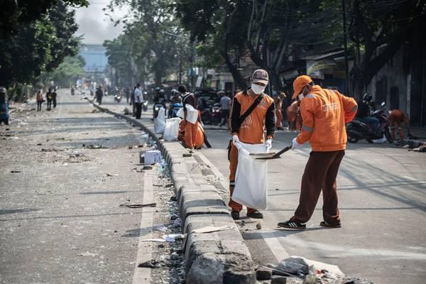 Petugas PPSU membersihkan jalan dari pecahan kaca pascabentrok polisi dan massa perusuh, di Jalan KS Tubun, Petamburan, Jakarta, Rabu (22/5/2019). - Antara