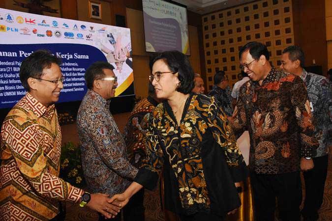 Menteri Keuangan Sri Mulyani Indrawati (tengah) didampingi Dirjen Pajak Robert Pakpahan (kedua kanan) menyalami para direksi BUMN dan instansi seusai penandatanganan perjanjian kerja sama pembinaan UMKM melalui program Business Development Services DJP di Jakarta, Selasa (30/4/2019). - ANTARA/Indrianto Eko Suwarso