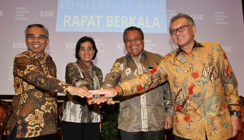 Menkeu Sri Mulyani Indrawati (kedua kiri) bertumpu tangan dengan Ketua Dewan Komisioner OJK Wimboh Santoso (dari kiri), Gubernur Bank Indonesia Perry Warjiyo, dan Ketua Dewan Komisioner LPS Halim Alamsyah, usai memberikan penjelasan mengenai hasil rapat berkala KSSK, di Jakarta, Selasa (23/4/2019). - Bisnis/Dedi Gunawan