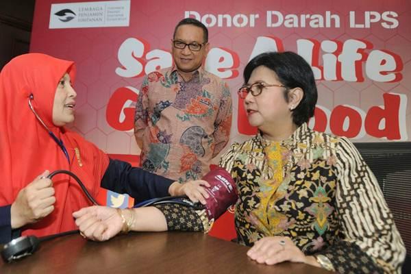 Anggota Dewan Komisioner Lembaga Penjamin Simpanan (LPS) Destry Damayanti (kanan), disaksikan Direktur Didik Madiono (tengah) memeriksakan kesehatan saat meninjau kegiatan donor darah dalam rangkaian perayaan Hari Ulang Tahun ke-12 LPS, di Jakarta, Selasa (5/9). - JIBI/Dedi Gunawan