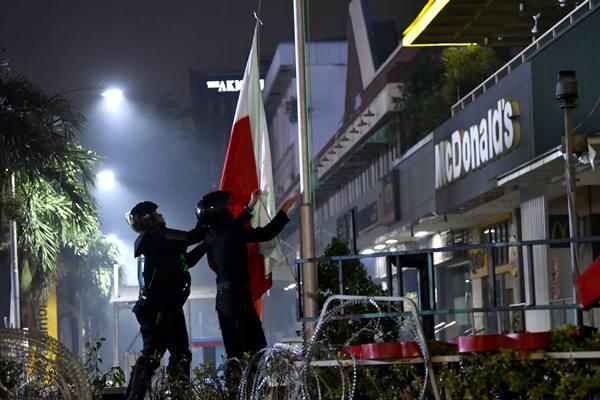 Anggota Brimob memasang bendera Merah Putih di kawasan Sarinah, Jl MH Thamrin saat unjuk rasa, Rabu (22/5/2019). - Antara