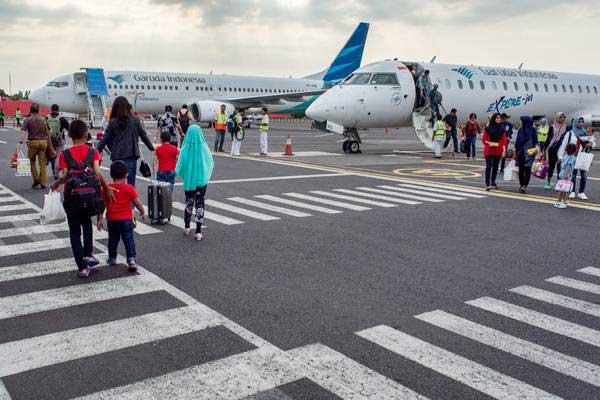 Penumpang berjalan di area parkir pesawat saat tiba di Bandara Ahmad Yani, Semarang, Jawa Tengah, Minggu (18/6/2017). - Antara/Aji Styawan
