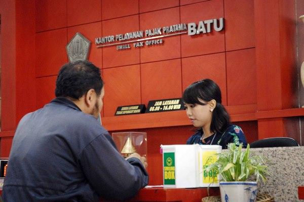 Petugas pajak melayani wajib pajak yang meminta informasi di Kanwil DJP Jatim III Malang, Selasa (20/10/2015). Penerimaan pajak sampai saat ini sudah mencapai 60,58% dari target Rp21,4 triliun yang menunjukkan tingkat kesadaran masyarakat membayar pajak semakin tinggi. - Bisnis/Choirul Anam