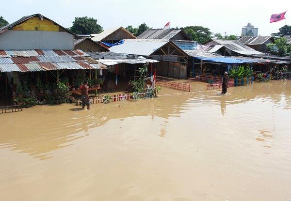 Ilustrasi - Warga melintas di depan tempat tinggalnya yang terendam banjir akibat meluapnya sungai Cisadane di kawasan Karawaci, Tangerang, Banten, Jumat (26/4/2019). Hujan deras dengan intensitas tinggi di kawasan Bogor Jawa Barat yang menyebabkan sunga Cisadane meluap hingga menyebabkan banjir di kawasan tersebut./ANTARA FOTO - Muhammad Iqbal
