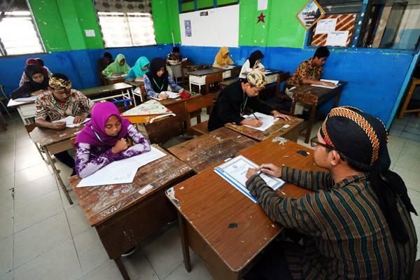 Sejumlah pelajar berbusana adat tradisional saat mengikuti Ujian Sekolah Berstandar Nasional (USBN) di SMP Muhammadiyah 11 Surabaya, Jawa Timur, Sabtu (21/4). Hal itu dalam rangka memperingati Hari Kartini. - Antara