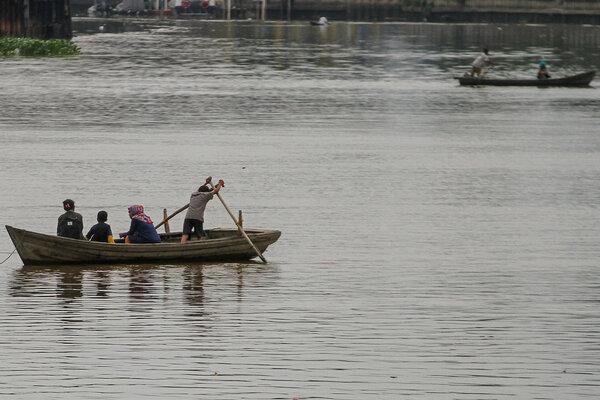 Sejumlah warga menyebrangi sungai Siak menggunakan jasa penyebrangan ojek sampan di Pekanbaru, Riau, Rabu (8/5/2019). Dengan adanya pembangunan infrastruktur jembatan yang semakin banyak di kawasan itu, membuat masyarakat mulai meninggalkan moda transportasi ojek sampan tersebut. - Antara/Rony Muharrman