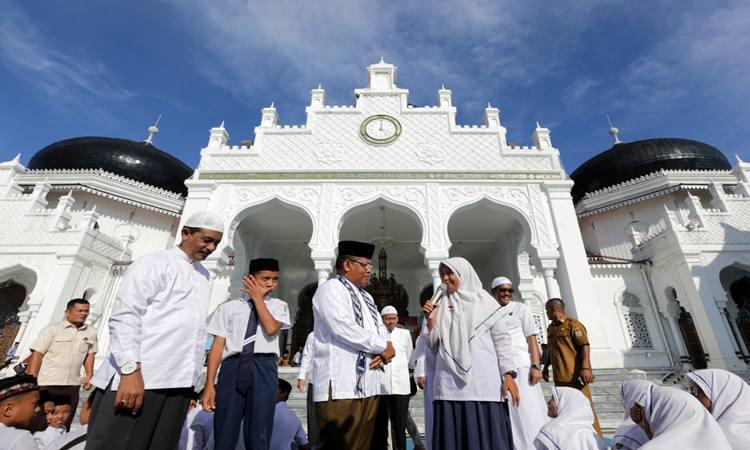 Wali Kota Banda Aceh Aminullah Usman (tengah) berdialog dengan pelajar Sekolah Menengah Pertama (SMP) saat mengikuti doa bersama jelang Ujian Sekolah Berstandar Nasional (USBN) dan Ujian Nasional (UN) di Masjid Raya Baiturrahman, Banda Aceh, Senin (8/4/2019). Doa bersama dan zikir yang diikuti para pelajar dari seluruh SMP di kota Banda Aceh itu untuk menguatkan mental dan spiritual siswa dalam menghadapi USBN dan UN tahun pelajaran 2018/2019. -  ANTARA FOTO/Irwansyah Putra.