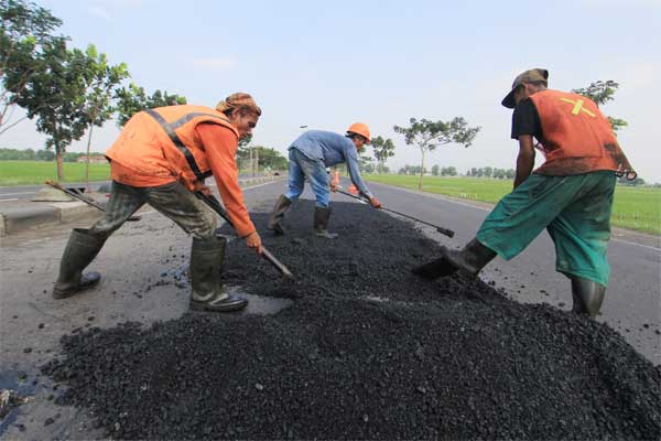 Pekerja menyelesaikan penambalan jalur pantura di Arjawinangun, Cirebon, Jawa Barat, Sabtu (10/6). - Antara/Dedhez Anggara