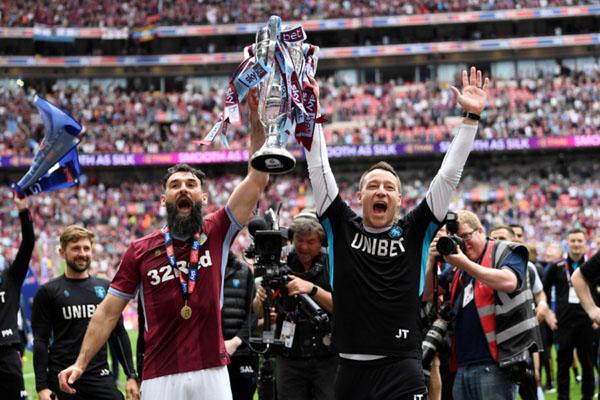 John Terry, asisten pelatih Aston Villa (kanan), bersama gelandang Mile Jedinak mengangkat trofi yang menandai kembalinya klub Birmingham tersebut ke Liga Primer Inggris setelah tiga musim absen. - Reuters