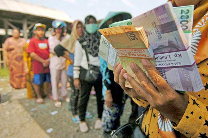 Warga antre menukarkan uang baru dari mobil penukaran uang Bank Indonesia, di Tempat Pelelangan Ikan (TPI) Pelabuhan Jongor, Tegal, Jawa Tengah, Kamis (16/5/2019). - ANTARA/Oky Lukmansyah