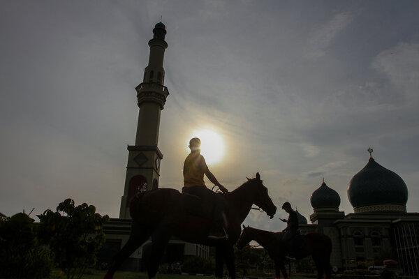Pengunjung menunggang kuda yang disediakan saat program wisata berkuda di Masjid Raya An-nur Pekanbaru, Riau, Selasa (14/5/2019). Program wisata berkuda ini difungsikan untuk memberi edukasi kepada masyarakat tentang olahraga berkuda sekaligus menjadi wisata jelang waktu berbuka puasa di bulan Ramadhan. - Antara/Rony Muharrman
