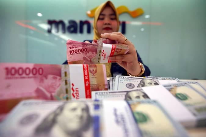 Karyawati Bank Mandiri menghitung mata uang dolar AS dan rupiah - Bisnis/Abdullah Azzam