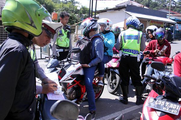 Anggota Polres Bogor melakukan razia kendaraan di jalur wisata kawasan Puncak, Gadog, Kabupaten Bogor, Jawa Barat, Selasa (28/3). - Antara/Yulius Satria Wijaya