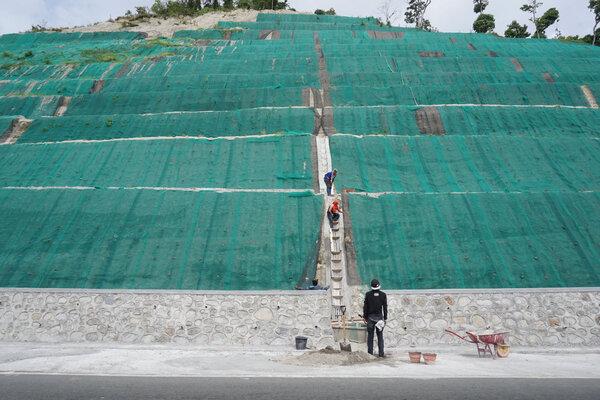 Sejumlah pekerja beraktivitas di proyek pengerasan lereng jalur Trans Sulawesi poros Palu-Toboli di Kawasan Pegunungan Kebun Kopi, Sulawesi Tengah, Selasa (14/5/2019). Jalur penghubung Kota Palu dengan sejumlah Kabupaten serta Provinsi Gorontalo dan Manado itu merupakan salah satu jalur yang akan dilalui pemudik Lebaran 2019. - Antara/Mohamad Hamzah.
