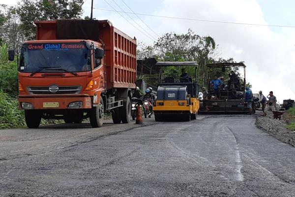 Petugas melakukan pengerjaan perbaikan jalan di Km 92 Desa Kandang Ayam, Kecamatan Babat Supat, Kabupaten Musi Banyuasin, Sumsel. - Bisnis/Dinda Wulandari