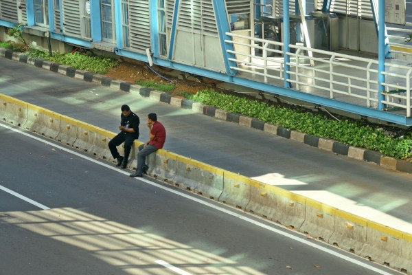 Dua warga duduk di atas beton pemisah jalur TransJakarta di Jalan MH Thamrin, Jakarta Pusat, Jumat (24/5/2019). - ANTARA FOTO/Aditya Pradana Putra