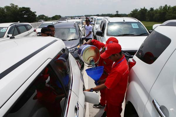 Petugas dari Pertamina mengisi BBM para peserta Ekspedisi Trans Jawa di rest area KM 597 B, Madiun, Jawa Timur, Kamis (20/12). - Bisnis/Nurul Hidayat