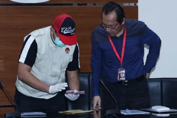 Penyidik menunjukan barang bukti uang disaksikan oleh Wakil Ketua KPK Saut Situmorang (kanan) saat konferensi pers terkait Operasi Tangkap Tangan kasus dugaan korupsi Direktur PT Krakatau Steel (Persero) di Gedung KPK, Jakarta, Sabtu (23/3/2019).  - ANTARA/Rivan Awal Lingga