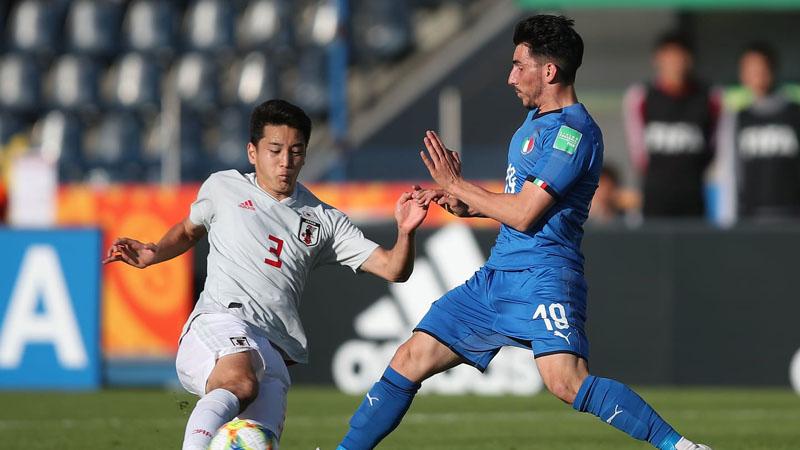 Bek Jepang Yuki Kobayashi (kiri) menghadang serangan ujung tombak Italia Domenico Alberico. - FIFA.com