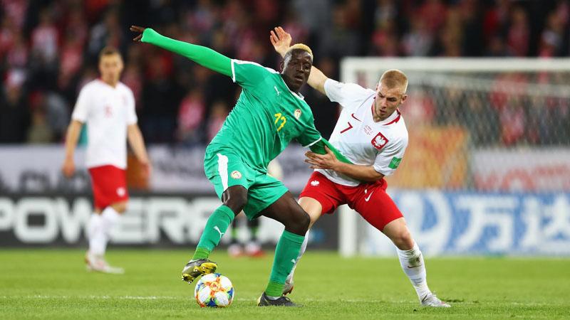 Gelandang Senegal Dion Lopy (kiri) berusaha mempertahankan bola yang hendak direbut gelandang Polandia Tomasz Makowski. Pertandingan berakhir tanpa gol dan kedua tim lolos ke 16 besar Piala Dunia U-20. - FIFA.com