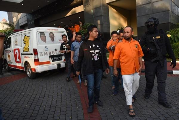 Petugas membawa tersangka pelaku kericuhan dalam aksi 22 Mei dalam rilis di Mapolda Metro Jaya, Jakarta, Kamis (23/5/2019). Selain menangkap sejumlah tersangka, Polisi juga mengamankan satu buah ambulan yang diduga disalahgunakan untuk membawa batu. - ANTARA FOTO / Akbar Nugroho Gumay