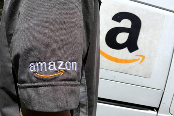 Seorang pengemudi Amazon.com Inc berdiri di samping truk di Los Angeles, California, Amerika Serikat. - Reuters
